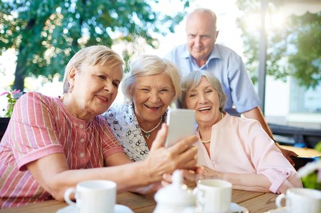 Moderne senioren, die foto von selbst machen