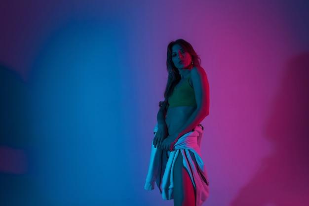 Moderne sexy junge frau in modischer jugendkleidung posiert drinnen mit neonviolett-blauer farbe im disco-stil. chic sinnliches mädchen steht im studio mit einem erstaunlichen stilvollen bunten licht.