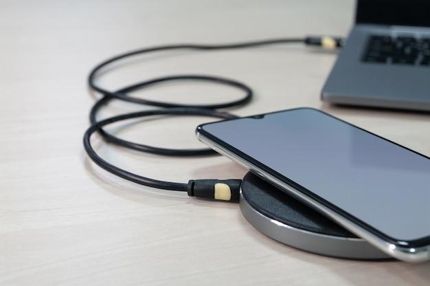 Moderne smartphones werden über ein kabelloses ladegerät aufgeladen