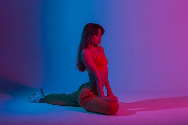 Moderne sportliche junge schöne frau in modischer jugendkleidung, die fitness in einem raum mit einem erstaunlichen hellen blauen licht macht. sportmädchen, das yoga-übungen im studio mit mehrfarbiger neonfarbe macht.