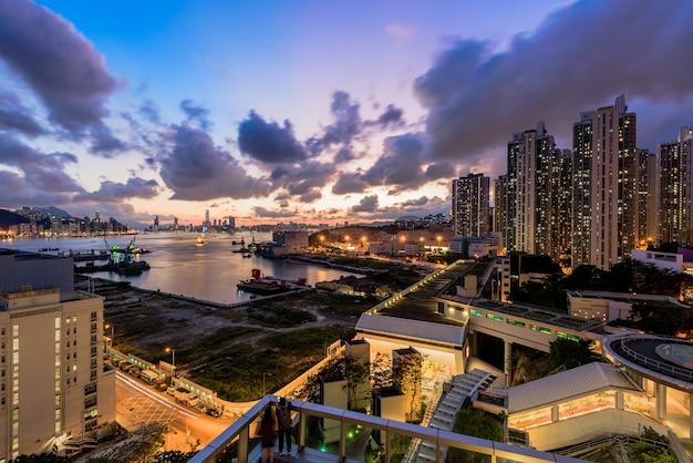 Moderne stadt mit häusern und gebäuden während des sonnenuntergangs