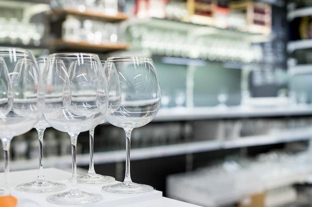 Moderne stielgläser zum verkauf im laden. brillen- und stielgläser-set. designer glaswaren auf einem glasregal in einem geschäft. set geschirr. moderne wohnkultur einrichtungsgeschäft. einkaufen im ladengeschäft.