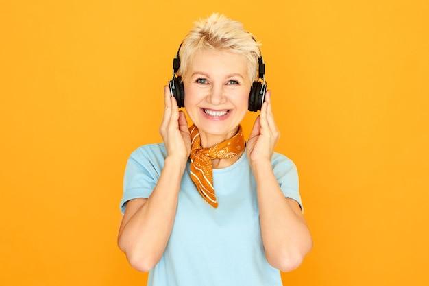 Moderne stilvolle kaukasische rentnerin mit kurzer frisur zum entspannen, die lieblingssongs über ohrhörer hört. attraktive reife frau, die schöne musik mit drahtlosen bluetooth-kopfhörern genießt