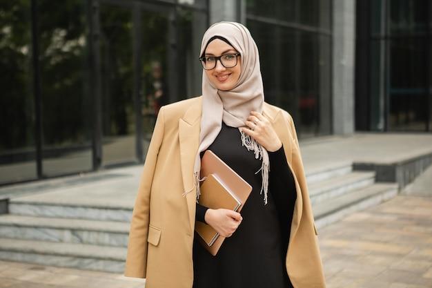 Moderne, stilvolle muslimische frau in hijab, business-stil-jacke und schwarzer abaya, die mit laptop in der stadtstraße spaziert