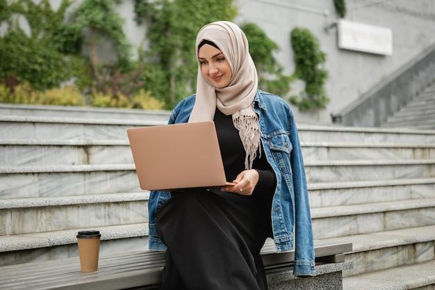 Moderne, stilvolle muslimische frau in hijab, jeansjacke und schwarzer abaya, die in der stadtstraße sitzt und am laptop arbeitet