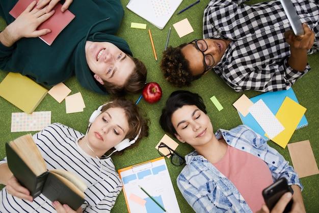 Moderne studenten, die geräte benutzen und bücher lesen