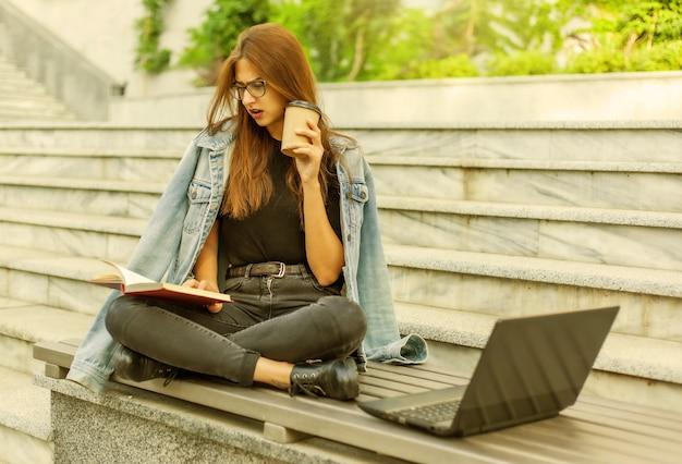 Moderne studenten. fernunterricht. junge begeisterte frau liest buch, während sie mit einem laptop auf der bank sitzt