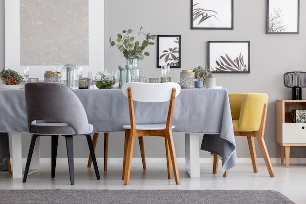 Moderne stühle am tisch mit geschirr im grauen esszimmerinnenraum mit postern und pflanzen