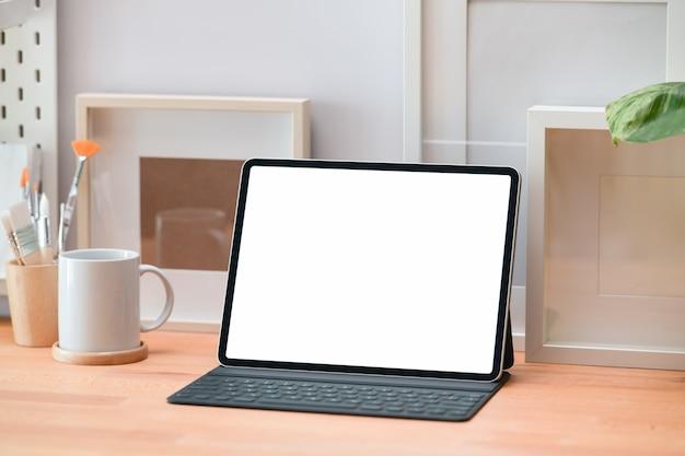 Moderne tablette und plakat des modells lank screen auf einem weißen arbeitsplatzschreibtisch