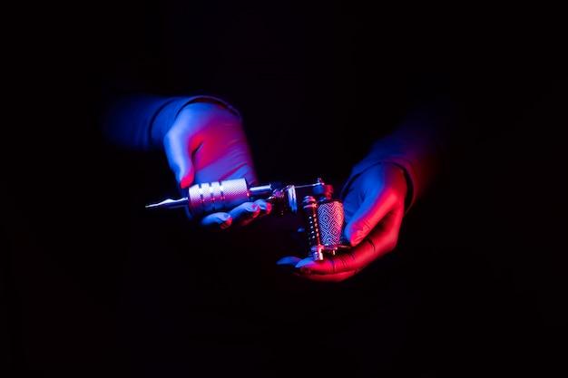 Moderne tätowiermaschine in weiblichen händen dauerhaft schön