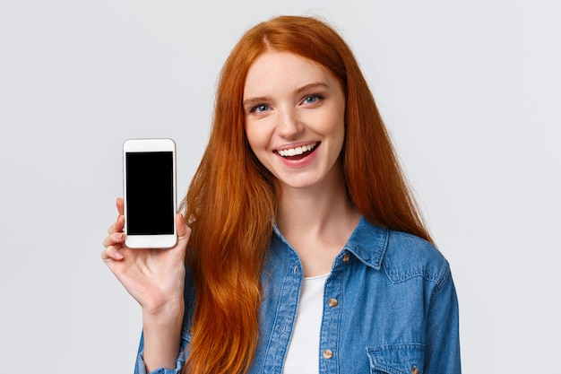 Moderne tausendjährige niedliche rothaarige frau des nahaufnahmeporträts mit blauen augen, rat bekommen coole neue app