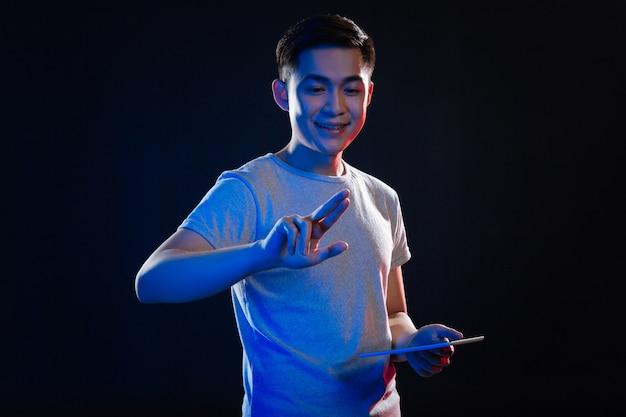 Moderne technologie. freudiger entzückter mann, der seine finger betrachtet, während er eine tablette hält