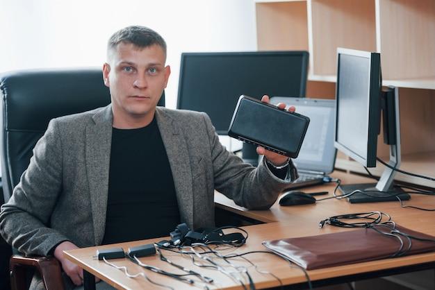 Moderne technologien. der polygraph-prüfer arbeitet im büro mit der ausrüstung seines lügendetektors