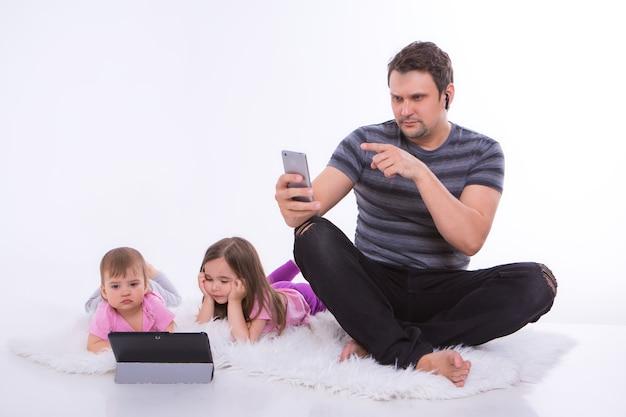 Moderne technologien im alltag: ein mann telefoniert über ein headset, kinder schauen sich einen cartoon auf einem tablet an. eltern mit mädchen auf dem boden