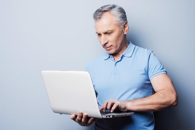 Moderne technologien immer griffbereit. fröhlicher älterer mann in lässiger holding laptop im stehen vor grauem hintergrund
