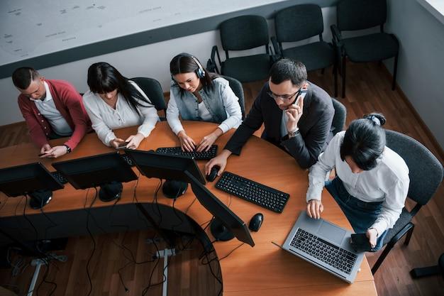 Moderne technologien machen das leben einfacher. junge leute, die im call center arbeiten. neue angebote kommen