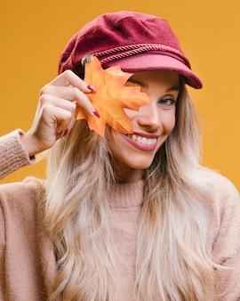 Moderne tragende kappe der jungen frau, die das ahornblatt betrachtet kamera hält