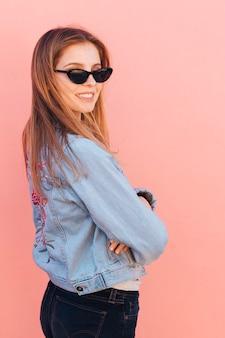 Moderne tragende sonnenbrille der jungen frau, die über schulter gegen rosa hintergrund schaut