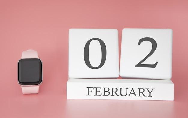 Moderne uhr mit würfelkalender und datum 02. februar auf rosa hintergrund. konzept winterzeit urlaub.