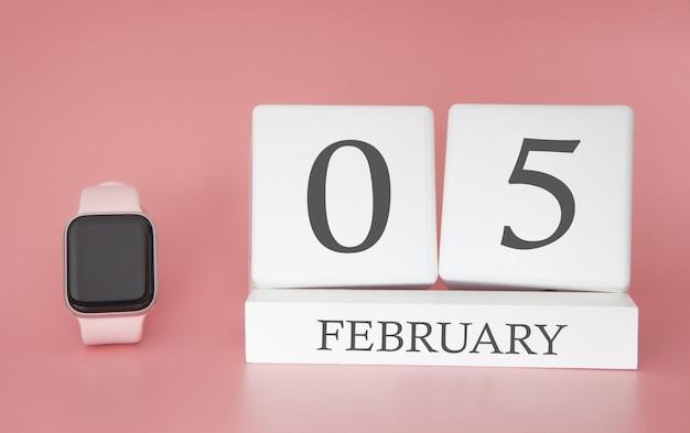 Moderne uhr mit würfelkalender und datum 05 februar auf rosa hintergrund. konzept winterzeit urlaub.
