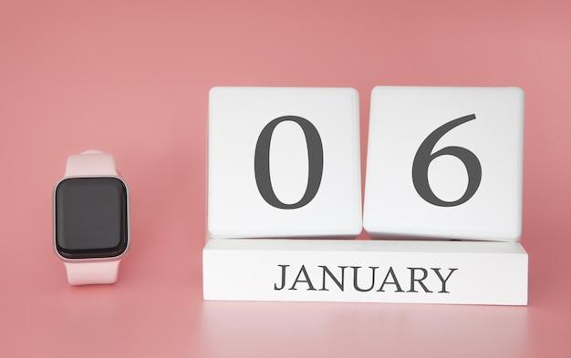 Moderne uhr mit würfelkalender und datum 06. januar auf rosa hintergrund. konzept winterzeit urlaub.