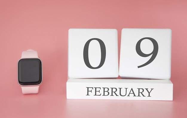 Moderne uhr mit würfelkalender und datum 09. februar auf rosa hintergrund. konzept winterzeit urlaub.