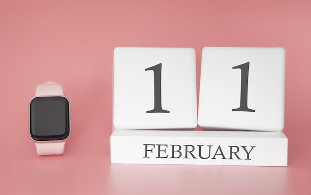 Moderne uhr mit würfelkalender und datum 11. februar auf rosa hintergrund. konzept winterzeit urlaub.