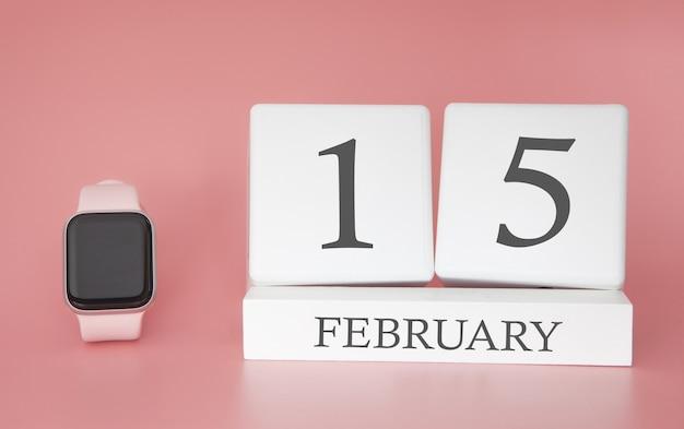 Moderne uhr mit würfelkalender und datum 15. februar auf rosa hintergrund. konzept winterzeit urlaub.