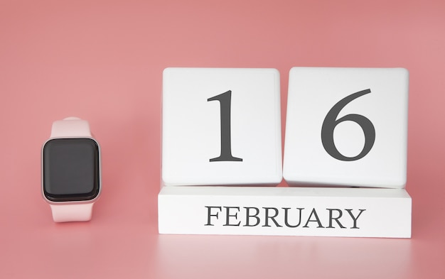 Moderne uhr mit würfelkalender und datum 16. februar auf rosa hintergrund. konzept winterzeit urlaub.