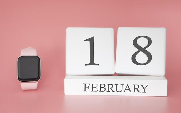 Moderne uhr mit würfelkalender und datum 18. februar auf rosa hintergrund. konzept winterzeit urlaub.