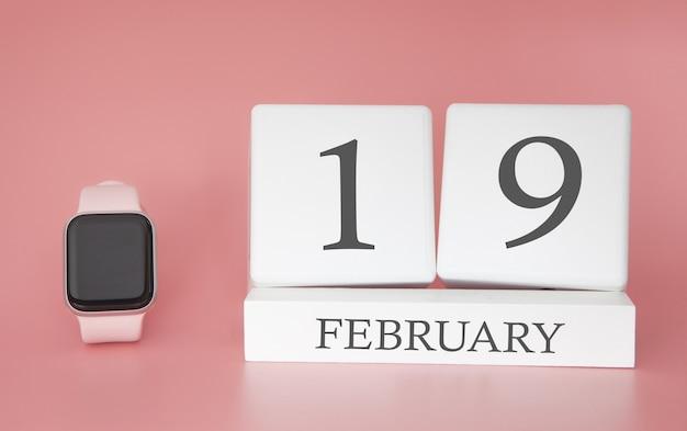 Moderne uhr mit würfelkalender und datum 19. februar auf rosa hintergrund. konzept winterzeit urlaub.