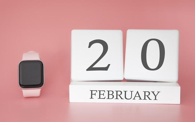 Moderne uhr mit würfelkalender und datum 20. februar auf rosa hintergrund. konzept winterzeit urlaub.