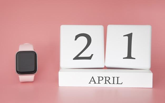 Moderne uhr mit würfelkalender und datum 21. april auf rosa hintergrund. konzept frühlingszeit urlaub.
