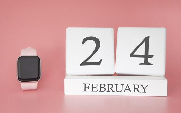 Moderne uhr mit würfelkalender und datum 24. februar auf rosa hintergrund. konzept winterzeit urlaub.