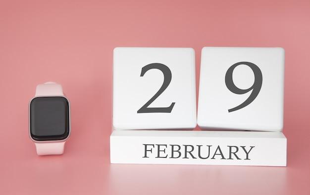 Moderne uhr mit würfelkalender und datum 29. februar auf rosa hintergrund. konzept winterzeit urlaub.