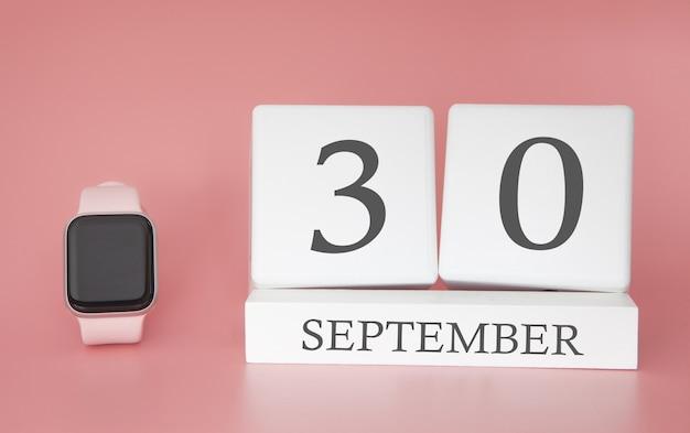 Moderne uhr mit würfelkalender und datum 30. september auf rosa wand. konzept herbstzeit urlaub.