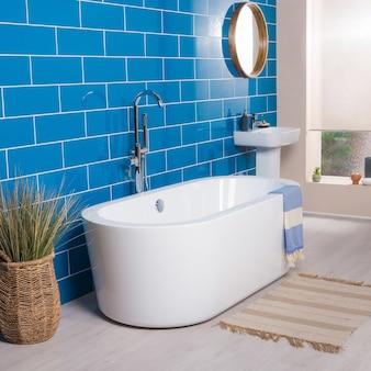 Moderne und neue stahlarmatur mit der keramikbadewanne im bad