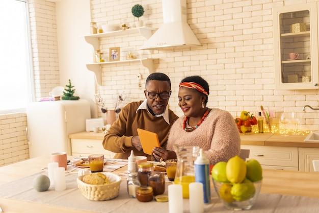 Moderne unterhaltung. glückliches nettes paar, das zusammen sitzt und interessante videos anschaut