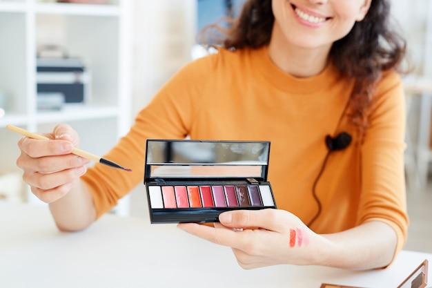 Moderne visagistin, die neue lippenstiftpalettenfarben testet und farbfelder auf ihrer hand macht, um sie zu demonstrieren