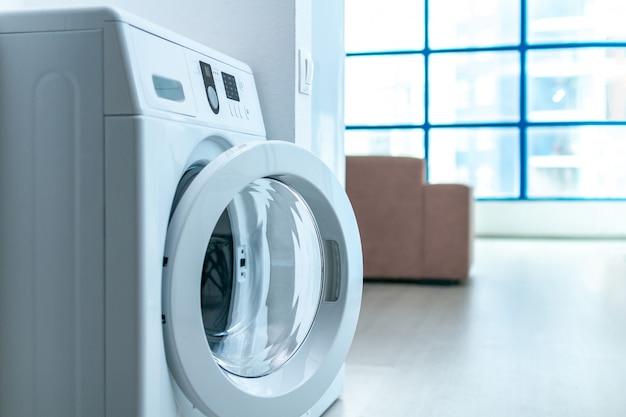 Moderne waschmaschine im raum in der wohnung. wäsche waschen zu hause.