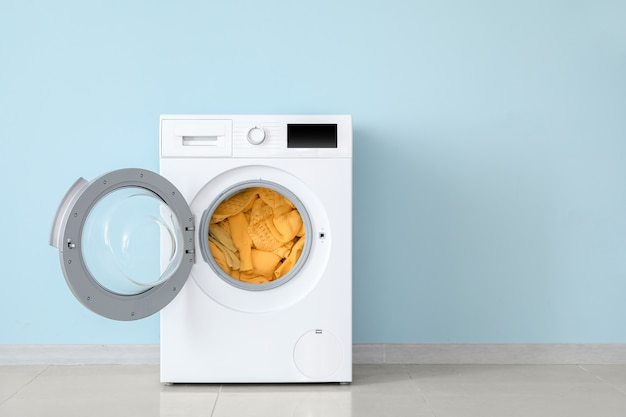 Moderne waschmaschine mit wäsche nahe farbwand