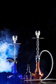 Moderne wasserpfeife mit rauch in der dunklen vereinslichtnahaufnahme