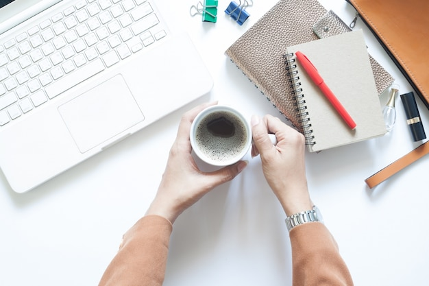 Moderne weiße büro-schreibtisch mit geschäftsfrau mit tasse kaffee, flat lay