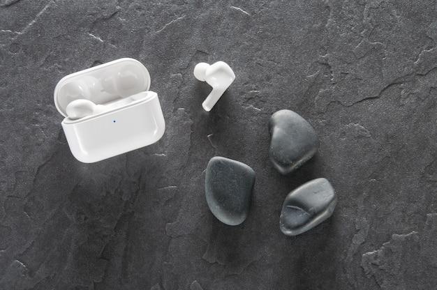 Moderne weiße kopfhörer auf steinhintergrund