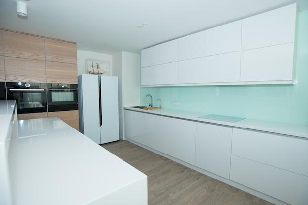 Moderne weiße küche mit holzplatten