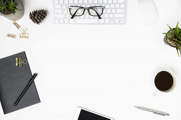 Moderne weiße schreibtischtabelle mit computergeräten, tasse kaffee und büroartikel. draufsicht mit kopienraum, flache lage.
