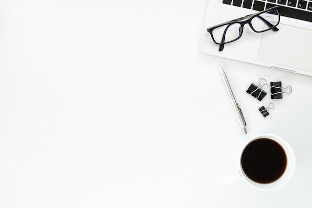 Moderne weiße schreibtischtabelle mit laptop, tasse kaffee und versorgungen in der ebenenlage.