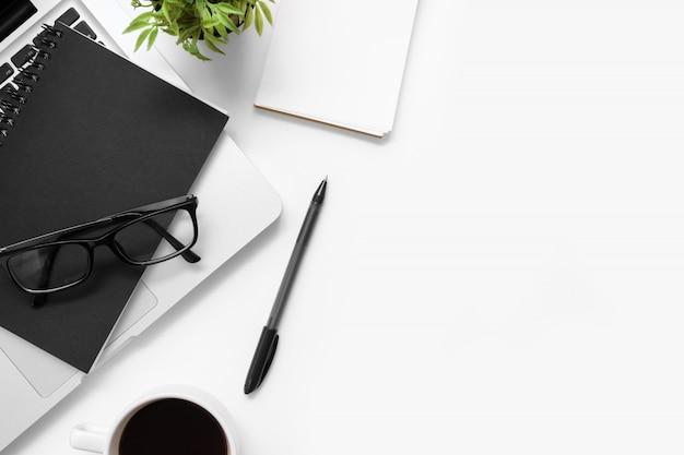 Moderne weiße schreibtischtabelle mit laptop und büroartikel. draufsicht mit kopienraum, flache lage.