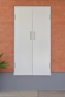 Moderne weiße tür auf backsteinmauerhintergrund