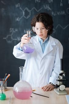 Moderne wissenschaft genießen. sorgfältig zufriedener talentierter schüler, der im labor steht und den chemieunterricht genießt, während er am wissenschaftlichen projekt teilnimmt